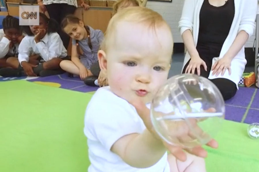 cnn baby holding clear glass orb children and adults in background